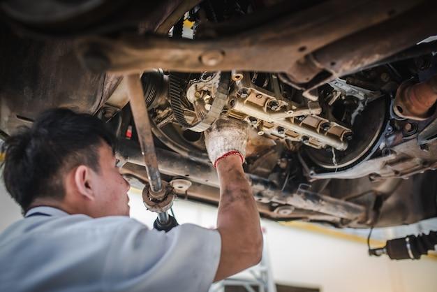 Механик работает для проверки автомобилей, которые работают в автосервисе с помощью вилочного погрузчика. ремонт и обслуживание автомобилей