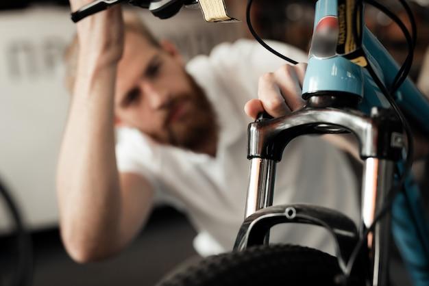 Mechanic looks at cycle details in bike workshop.