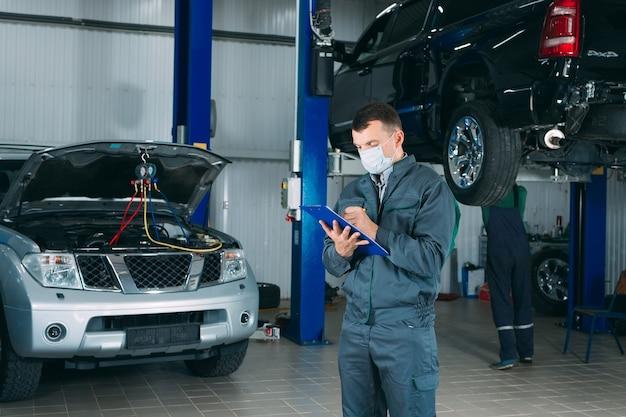 修理工場でクリップボードに車の記録を維持している整備士。