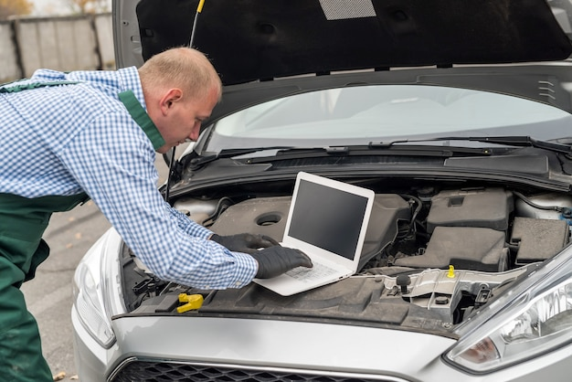 Mechanic making diagnostic of a car with laptop