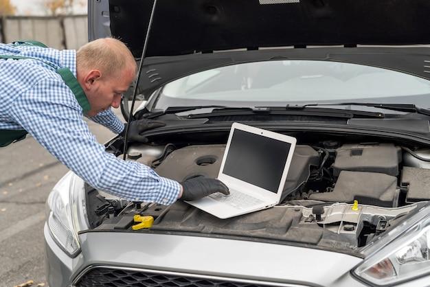 노트북으로 자동차를 진단하는 정비공