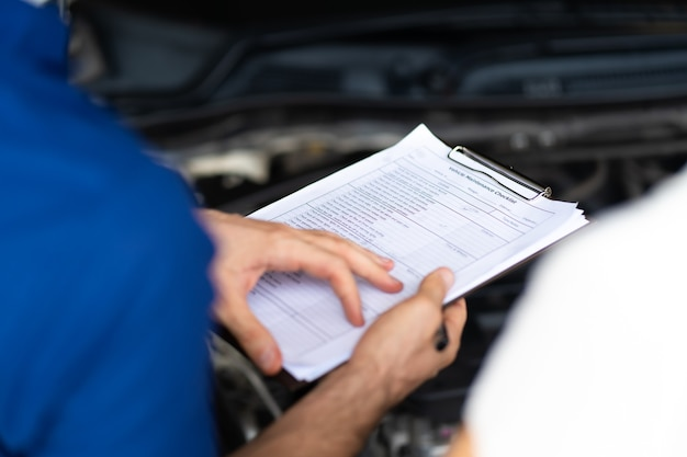 정비사 남자와 여자 고객은 배달 전에 자동차 상태를 확인합니다. 자동차 수리 정비소 차고.