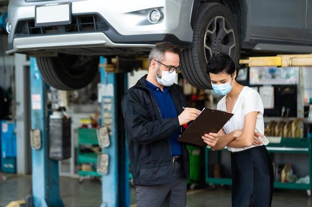 의료용 얼굴 마스크 보호 코로나바이러스를 착용한 정비사 남성과 여성 고객은 배달 전에 자동차 상태를 확인합니다.
