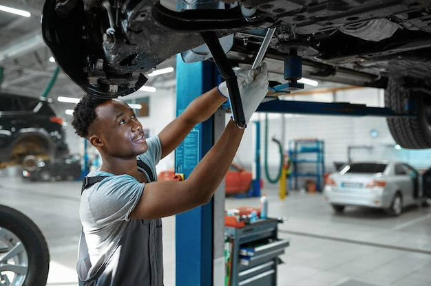 Mechanic man checks car suspension in mechanical workshop