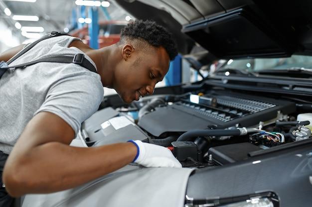 Mechanic man checks engine in mechanical workshop
