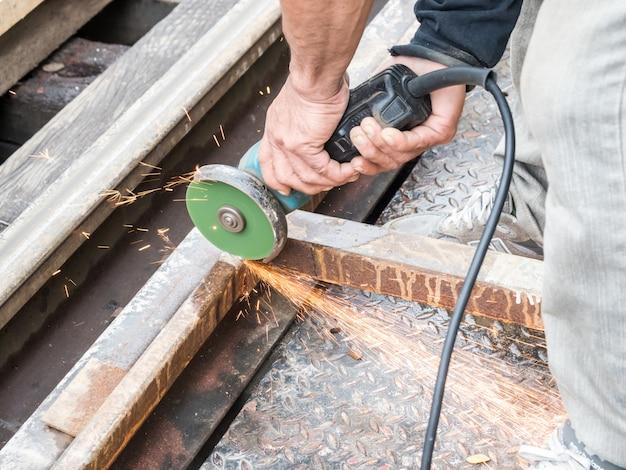 Mechanic man cutting metal with grinder spark
