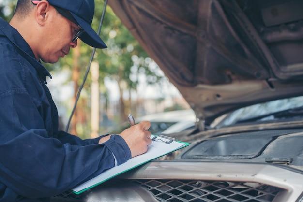 정비사는 자동차 센터를 위한 현장 서비스 자동 차고에서 야외에서 자동차 타이어를 확인합니다.