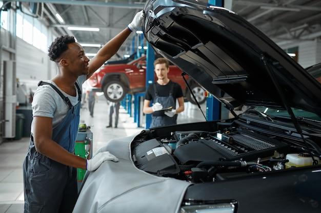 Механик осматривает двигатель в механической мастерской.