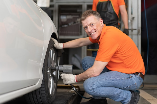 Mechanic man in orange shirt using pneumatic wrench tool to tighten a tire of car in auto service garage