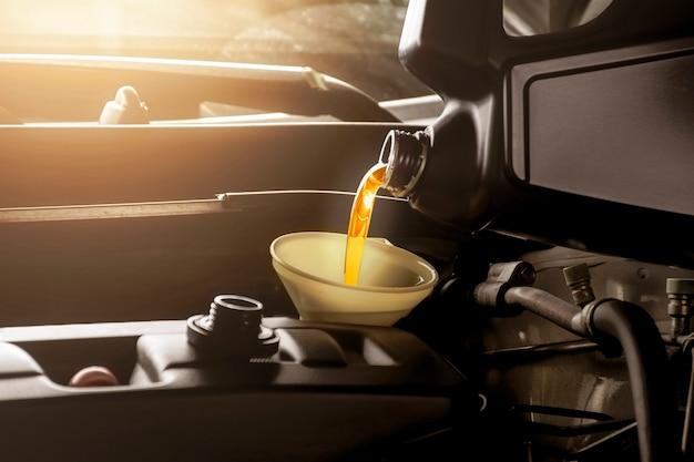 Механик наливает моторное масло в двигатель автомобиля