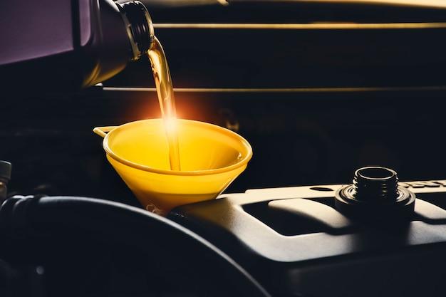 修理ガレージの車のエンジンに潤滑油を注ぐ整備士