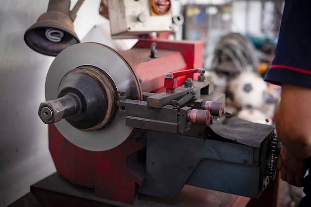 Механик, ремонтирующий тормоз, использует токарный станок, полируя дисковые тормоза