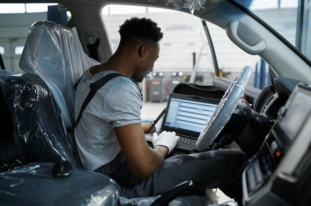 Механик, использующий ноутбук в машине с открытым капотом в механической мастерской