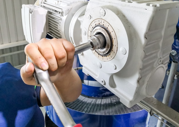 Mechanic man using a wrench to repair or maintain the drive motor at machine