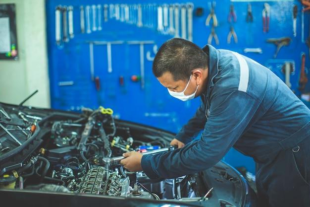 Механик с гаечным ключом. концепции инженера и ремонта автомобилей автомобильного двигателя грязные руки, держащие инструменты с помощью