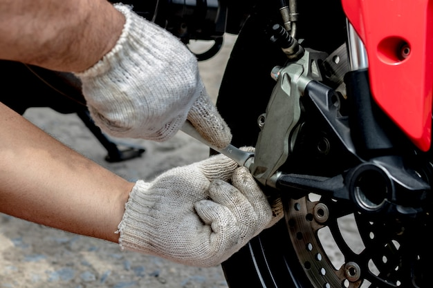 A mechanic people use hand are repairing a motorbike