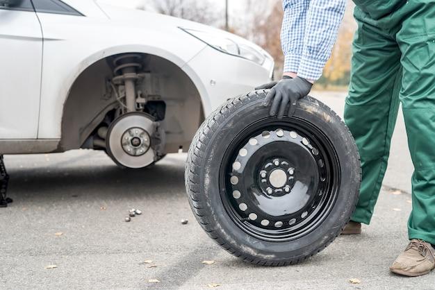 Mechanic posing with spare wheel on roadside