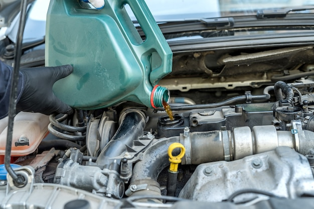 車のエンジンにオイルを注ぐ整備士。オートモーターサービス。修復