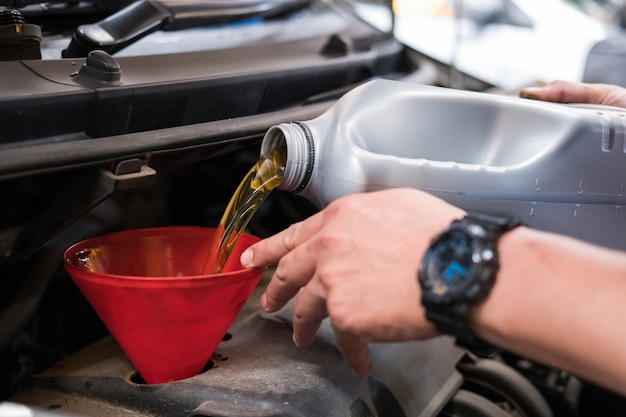 Mechanic pouring oil to vehicle engine.