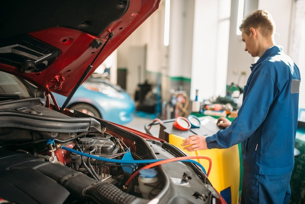 Mechanic pumps freon into the conditioning system