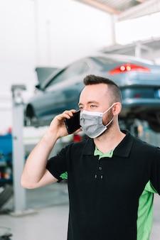외과용 마스크를 쓰고 자동차 부품을 구입하는 정비공