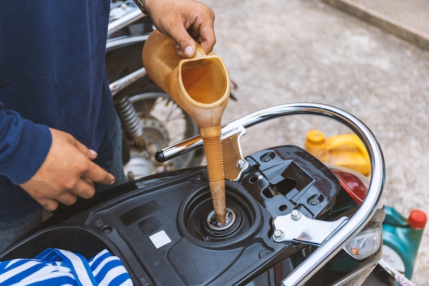 Mechanic refueling motorbike with soft-focus and over light in the background
