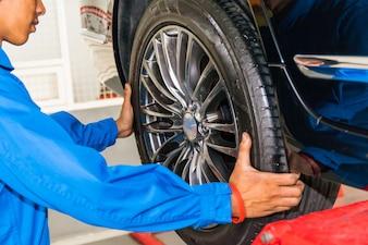 Mechanic removing or replacing car wheel at car service garage