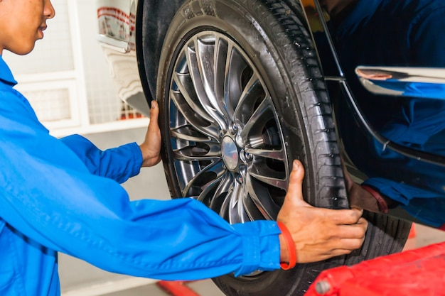 Mechanic removing or replacing car wheel at car service garage