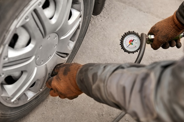 Mechanic at repair service station checking tyre pressure with gauge