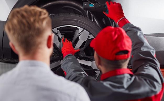 Механик, ремонтирующий автомобиль в мастерской