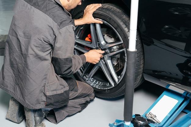 리프트 잭과 전기 드릴을 사용하여 자동차 수리점에서 자동차 바퀴를 수리하는 정비공