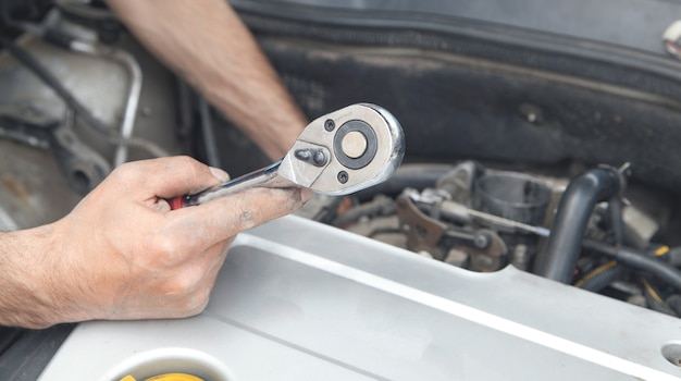 Mechanic repairing car with ratchet wrench.