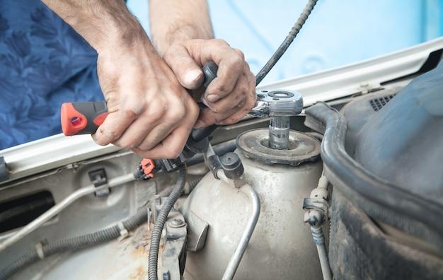 Механик ремонтирует автомобиль с храповым ключом.