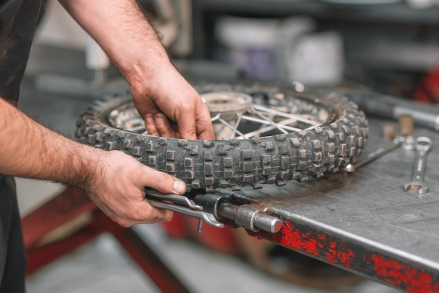 Mechanic repairing damaged motorcycle tire, in repair shop.