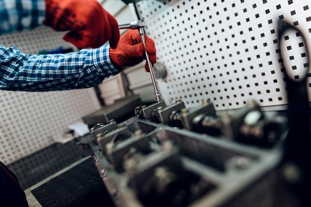 Mechanic repairing the engine in the workshop.