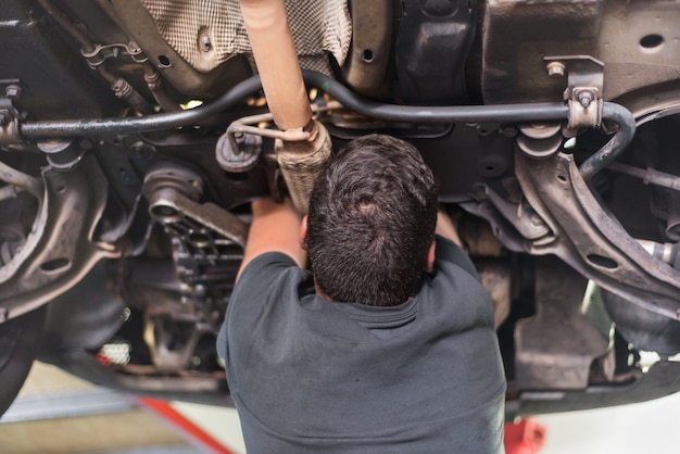 Mechanic repairing exhaust system