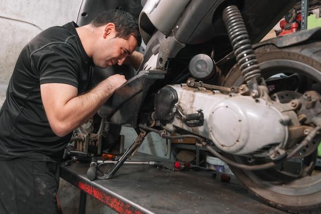 Mechanic repairing scooter motorbike in repair garage.