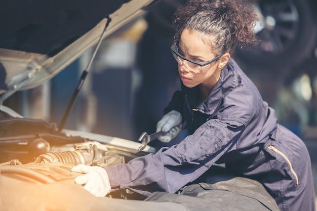 Механик, ремонтирующий двигатель или электрические части автомобиля в гараже
