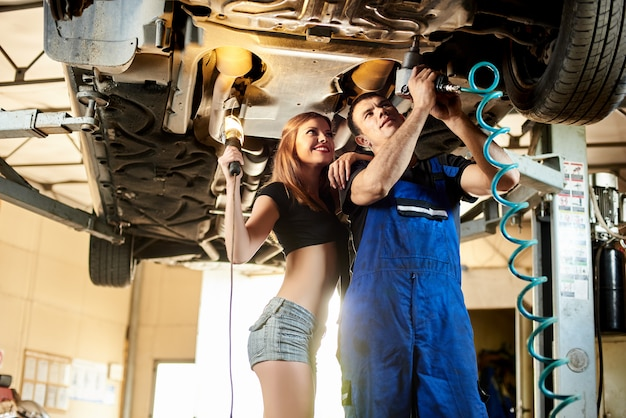 Mechanic repairs a lifted car in an automotive service