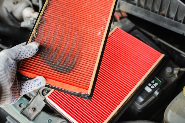 Mechanic replaces air filter in the car