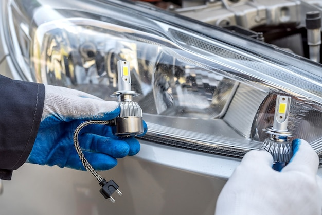 The mechanic replaces the halogen bulbs in the headlights in the car. auto technolgy