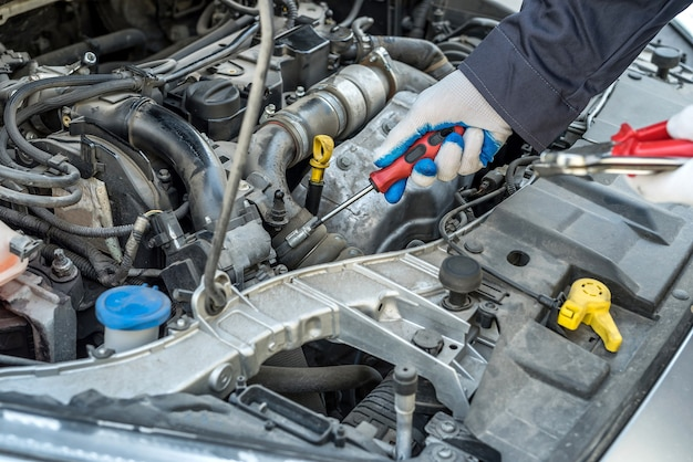 ドライバーの修理またはガレージで車をチェックする機械工の手。自動車サービス