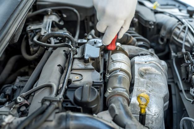 ドライバーの修理またはガレージで車をチェックする機械工の手