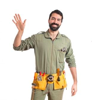 Mechanic saluting over white background
