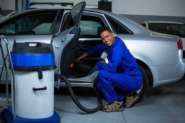 Механик обслуживание автомобилей с помощью пылесоса