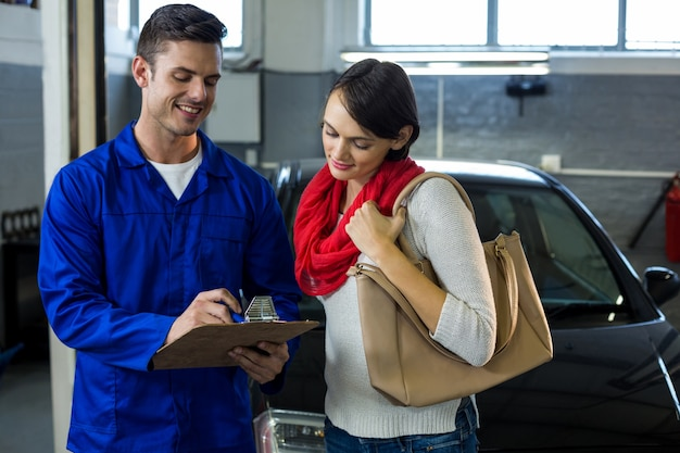 Mechanic showing check list to customer