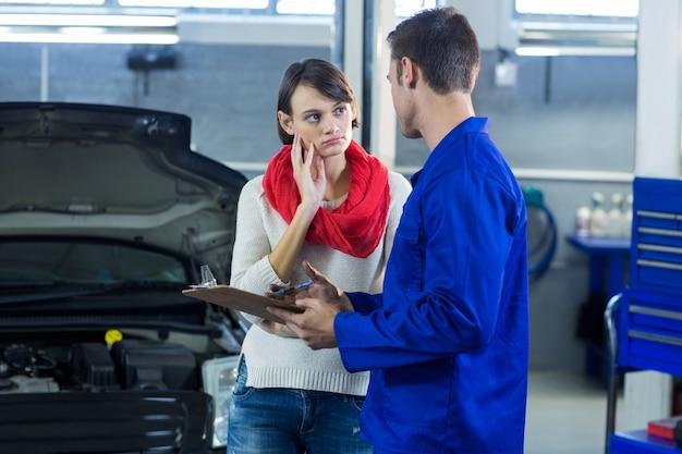 Mechanic showing check list to customer