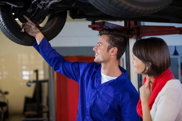 고객에게 자동차 문제를 보여주는 정비공
