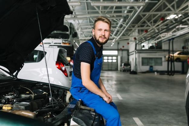 Механик сидит на машине в мастерской