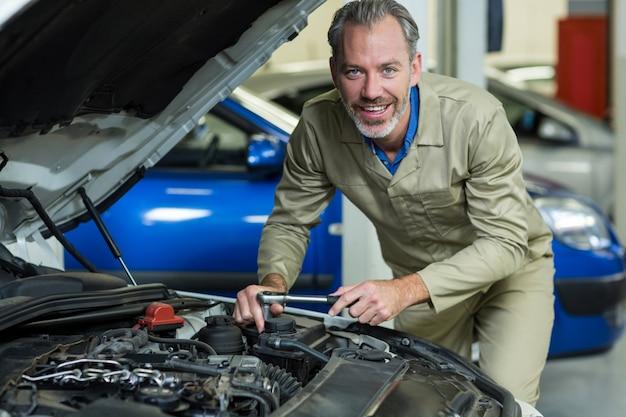Механик улыбается при обслуживании двигателя автомобиля